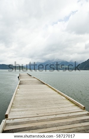 A wooden dock extendng into the lake in a cloudy day