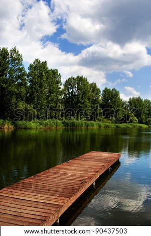 A wooden dock, pier, on a lake in summer sunny day, blue sky, white clouds, lake - stock photo