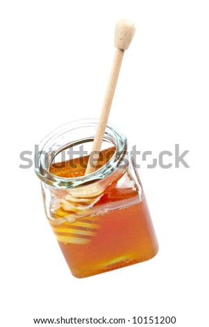 A wooden drizzler inside of honey jar, reflected on white background