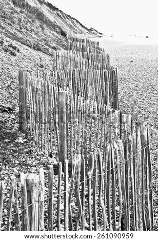 A wooden fence at the base of a cliff in the UK to protect against falling rocks, in black and white - stock photo