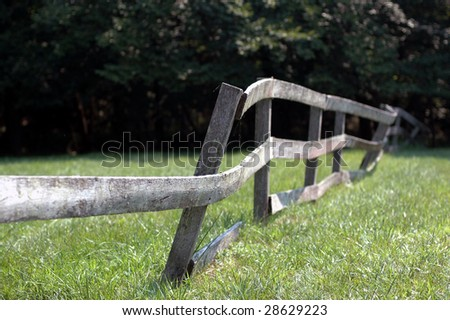A wooden fence in a field, missing a board and leaning. - stock photo