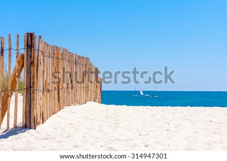 A wooden fence on a white sandy beach on a sunny day with clear blue sky - stock photo