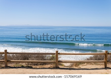 A wooden fence overlooking the Pacific ocean near Santa Barbara, California.  A coastal scene photographed at Rincon Park. - stock photo