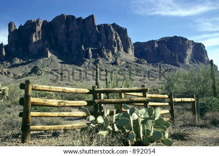 A wooden fence with the Superstition Mountains in the background. - stock photo
