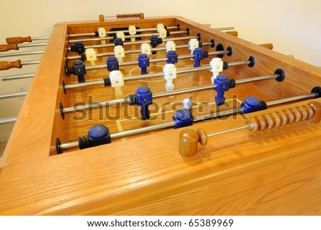A wooden foosball table close up.