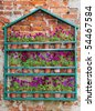 A wooden Frame against a red brick wall with rows of Flowerpots with Purple Pansies growing - stock photo