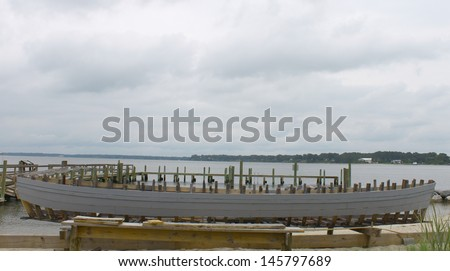 A wooden frame structure of a large boat being constructed (built) along a beach and a pier along the river on a cloudy hazy summer day in Yorktown Virginia - stock photo