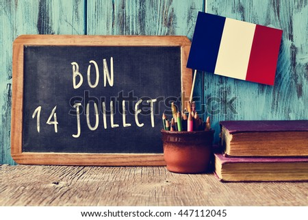 a wooden-framed chalkboard with the text bon 14 juillet, happy 14th of July, the National Day of France, written in French and a flag of France, against a rustic blue wooden background - stock photo