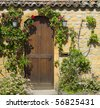 A wooden front door in the ancient stone house - stock photo
