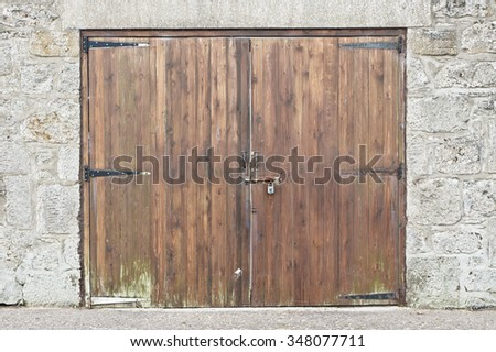 A wooden garage door in a stone wall - stock photo