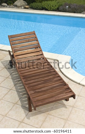 A wooden garden deckchair standing by the pool - stock photo