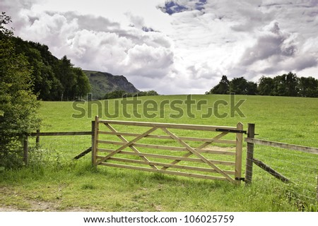 A wooden gate faces a green hilly lawn in the Lake District in a cloudy summer day - stock photo