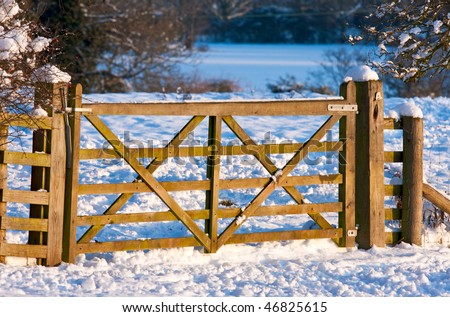 A wooden gate through snowy fields, in warm afternoon sunlight. - stock photo