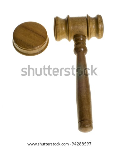 A wooden gavel rests beside a striker plate isolated on white - stock photo