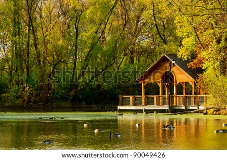 A Wooden Gazebo over a Beautiful Blue Pond in Autumn - stock photo