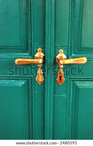 A wooden green door with two knobs - stock photo