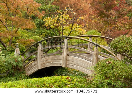 A wooden, Japanese-style arch bridge in a park with autumn foliage in the background - stock photo