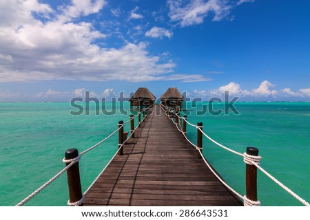 a wooden jetty leading to reed huts over the sea with a distant horizon and idyllic blue clouded sky - stock photo