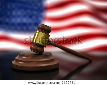 A Wooden Judge Gavel in Focus and American Flag Waving in Background - stock photo