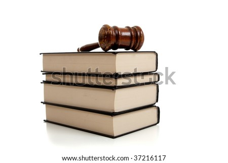 A wooden judges gavel on top of a stack of law books on white background - stock photo