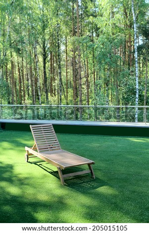 A wooden lounge chair on a green grass near a birchwood - stock photo