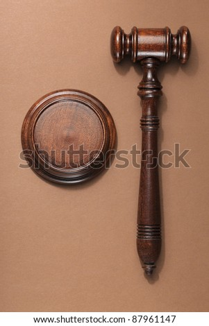 A wooden mahogany gavel with sound block on brown background. - stock photo