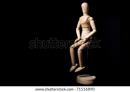 A wooden mannequin on a black background. - stock photo