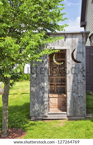 A wooden outhouse ideally located in the backyard. - stock photo