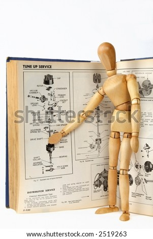 A wooden person teaching about a car repair from a technical manual - stock photo