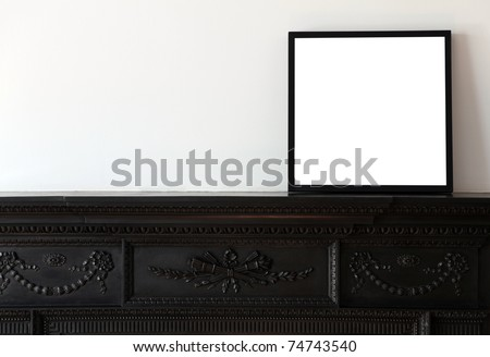 A wooden picture frame on a cast iron mantle piece. - stock photo