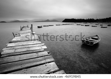a wooden pier and boats - stock photo