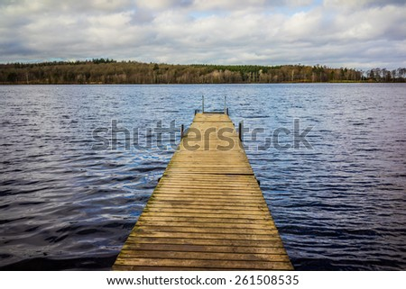 A wooden pier and lake, seen in daylight - stock photo