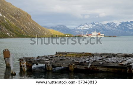 A wooden pier in the abandoned whaling station at Grytviken, South Georgia. Witness to a bloody past, it now provides rest for seals and birds to rest in peace. - stock photo