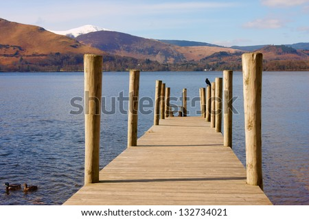 A wooden pontoon on a lake surrounded by mountains