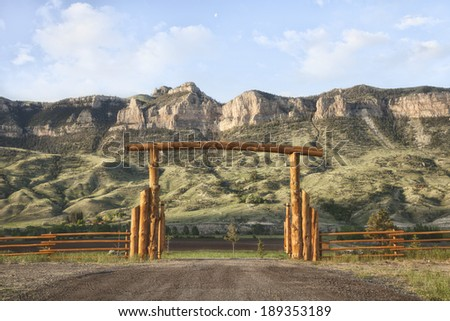 A wooden ranch gate in front of rocky cliffs in Wyoming, USA - stock photo