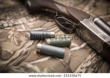 A wooden retro shotgun with shotgun shells - stock photo