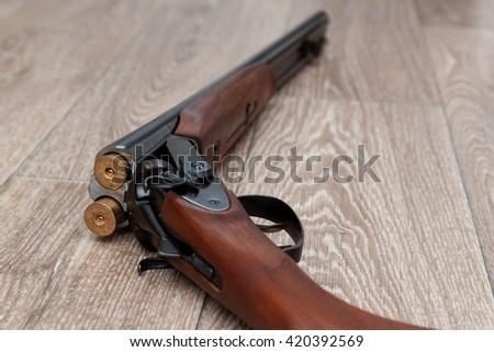 A wooden retro shotgun with shotgun shells on wooden background - stock photo