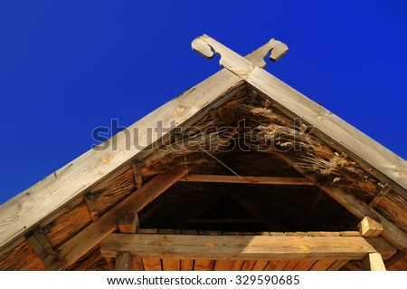 A wooden roof with an attic, covered with reeds - an element of Ukrainian national house