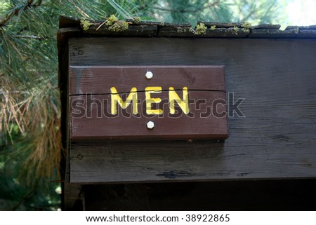 A wooden sign hung over the entrance to a men's room in a woodsy area - stock photo