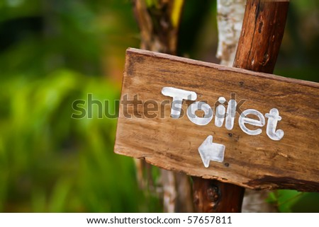 A wooden sign hung over the entrance to a toilet - stock photo