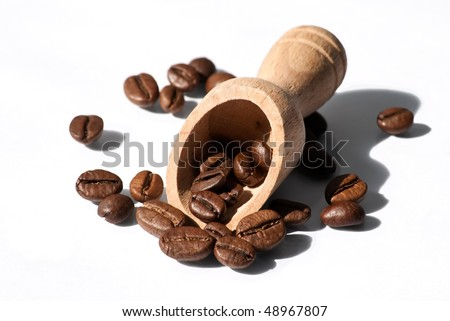 a wooden spoon and coffee beans