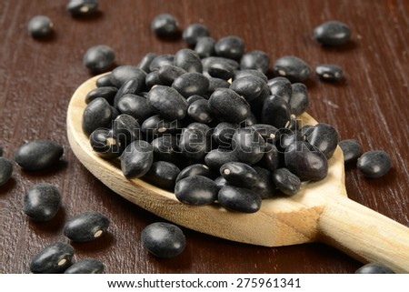 A wooden spoon full of turtle beans, shot close up - stock photo