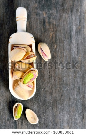 a wooden spoon of raw pistachio nuts on a old wooden background - stock photo