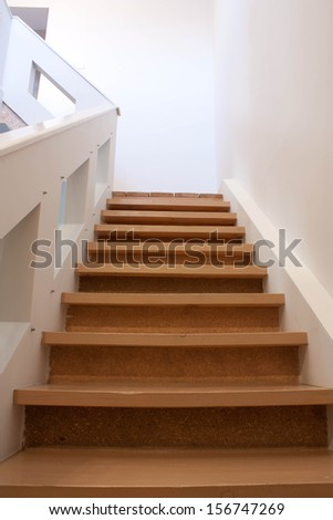 A wooden staircase with white railings and walls - stock photo
