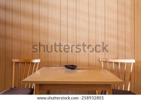 a wooden table against a wooden wall with two wooden chairs in the morning - stock photo