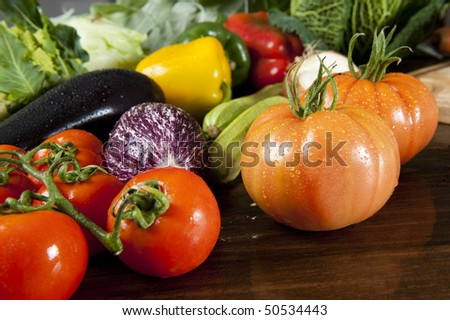 a wooden table spread of fresh vegetables - stock photo
