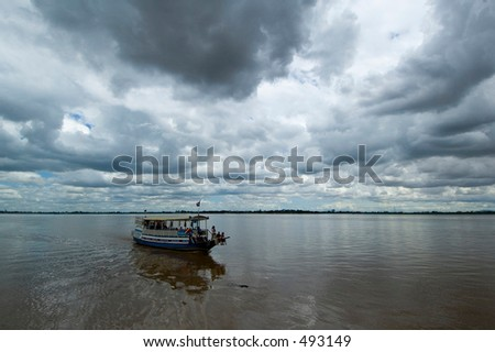 A wooden tourist cruise boat looks vulnerable as storm clouds gather over the Mekong, Cambodia