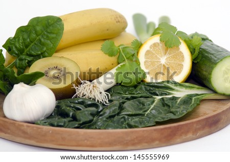 A wooden tray with Alkaline diet vegetables and fruits: Banana, kiwi, spinach, lemon, cucumber, parsley , silver beat and garlic. - stock photo