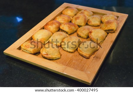 A wooden tray with some meat pattys. Patty translation to spanish is empanada or empanadilla - stock photo