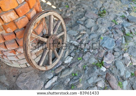 A wooden wagon wheel at the column of bricks